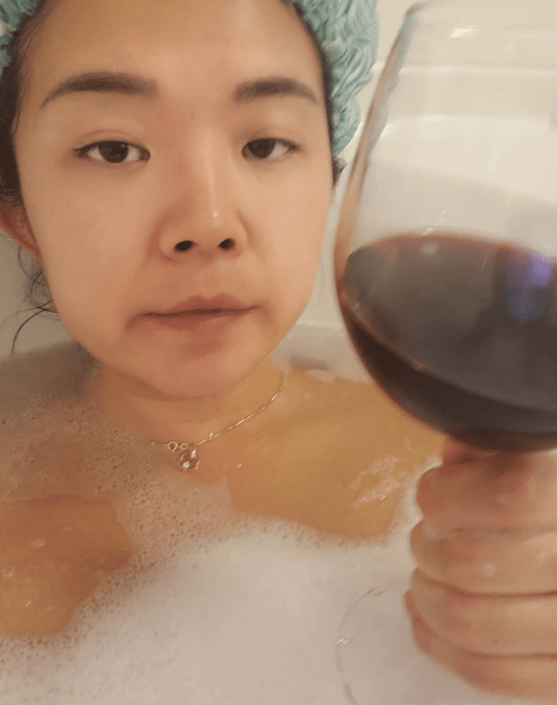 Rose holding a glass of wine while lounging in a bath tub