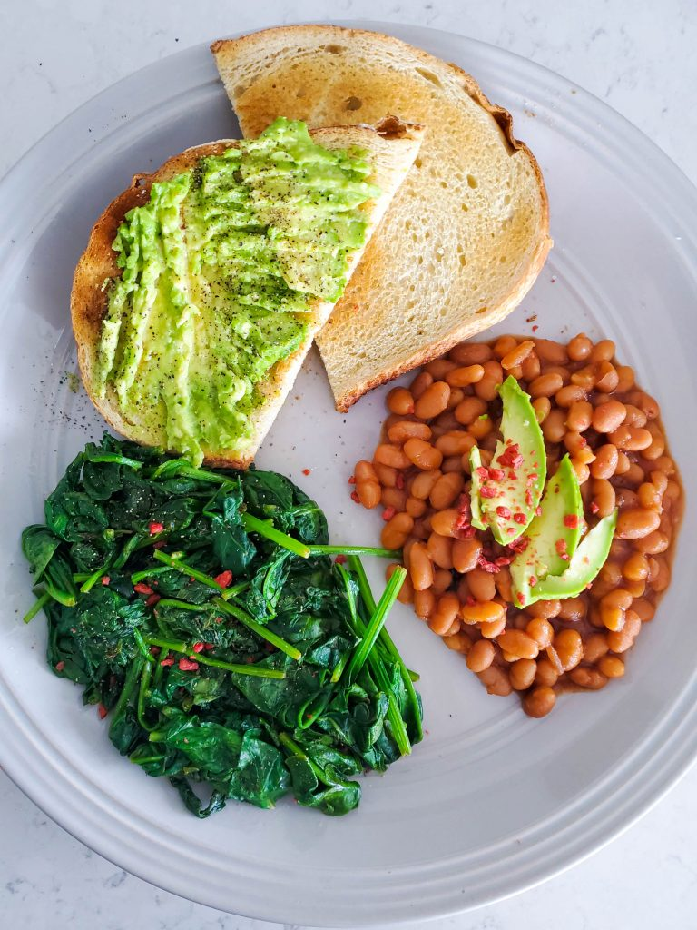 a photo of stir fried spinach, beans, and avocado toast on a plate for breakfast for what i ate in a day