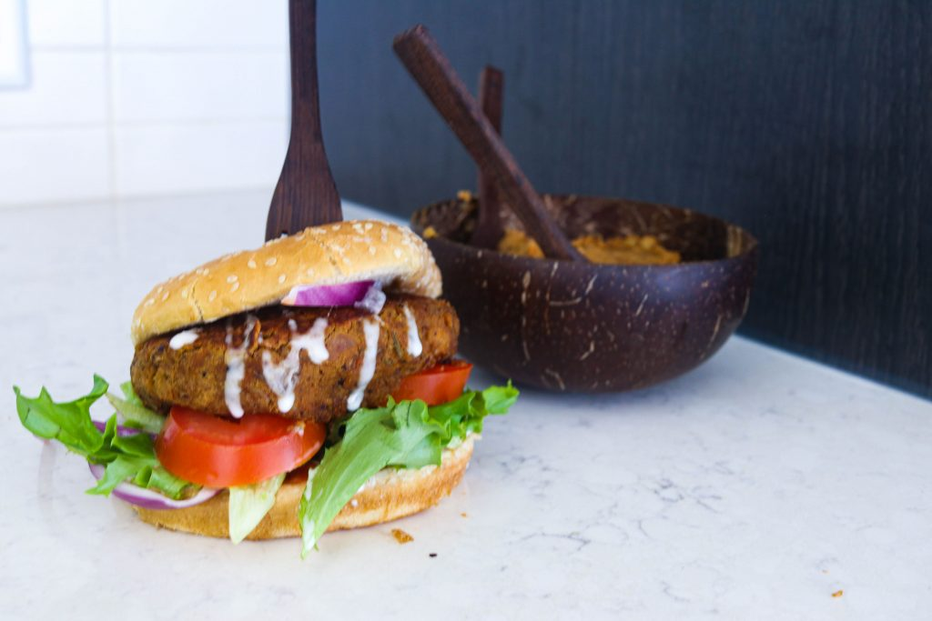 Photo of chickpea burger already assembled with a fork plunged in