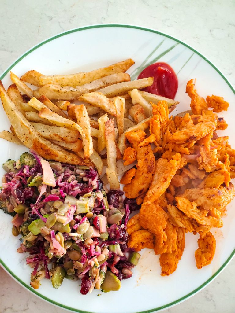 a plate filled with fries, soy curls, and salad --  an easy vegan meal to put together