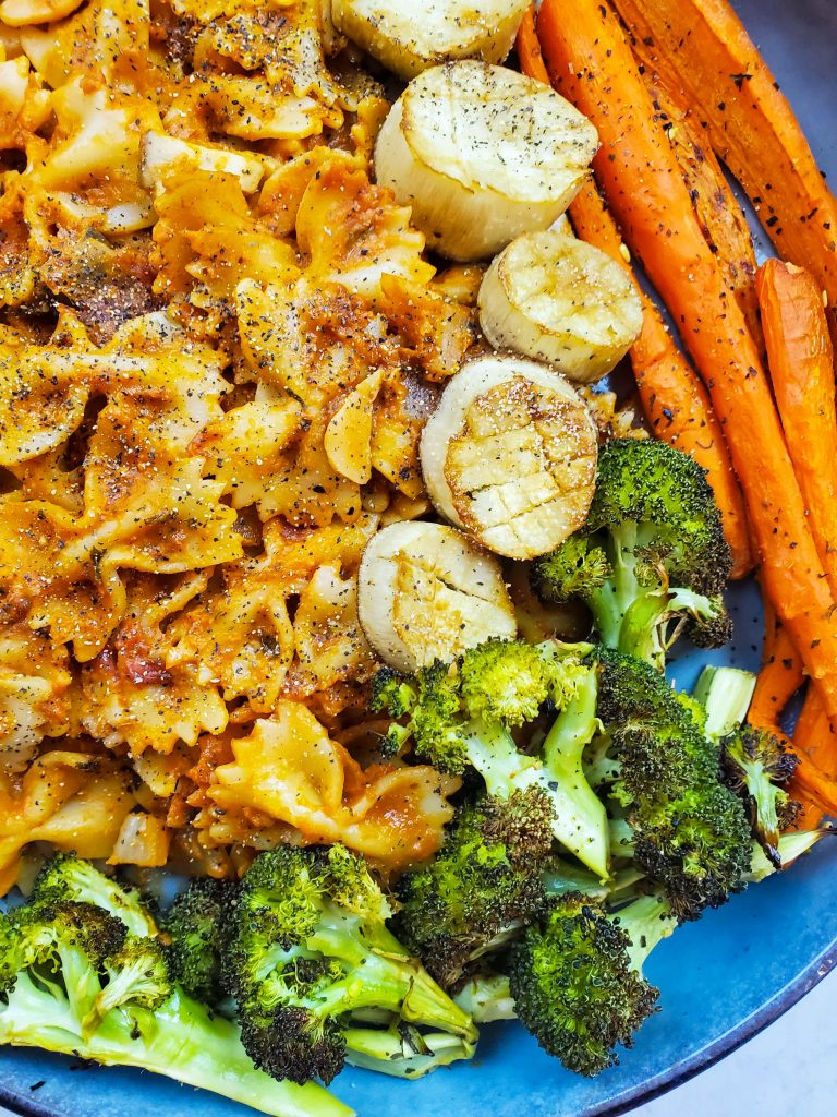 a close up photo of the vegan rosé pasta dish that also has roasted broccoli and carrots on the side