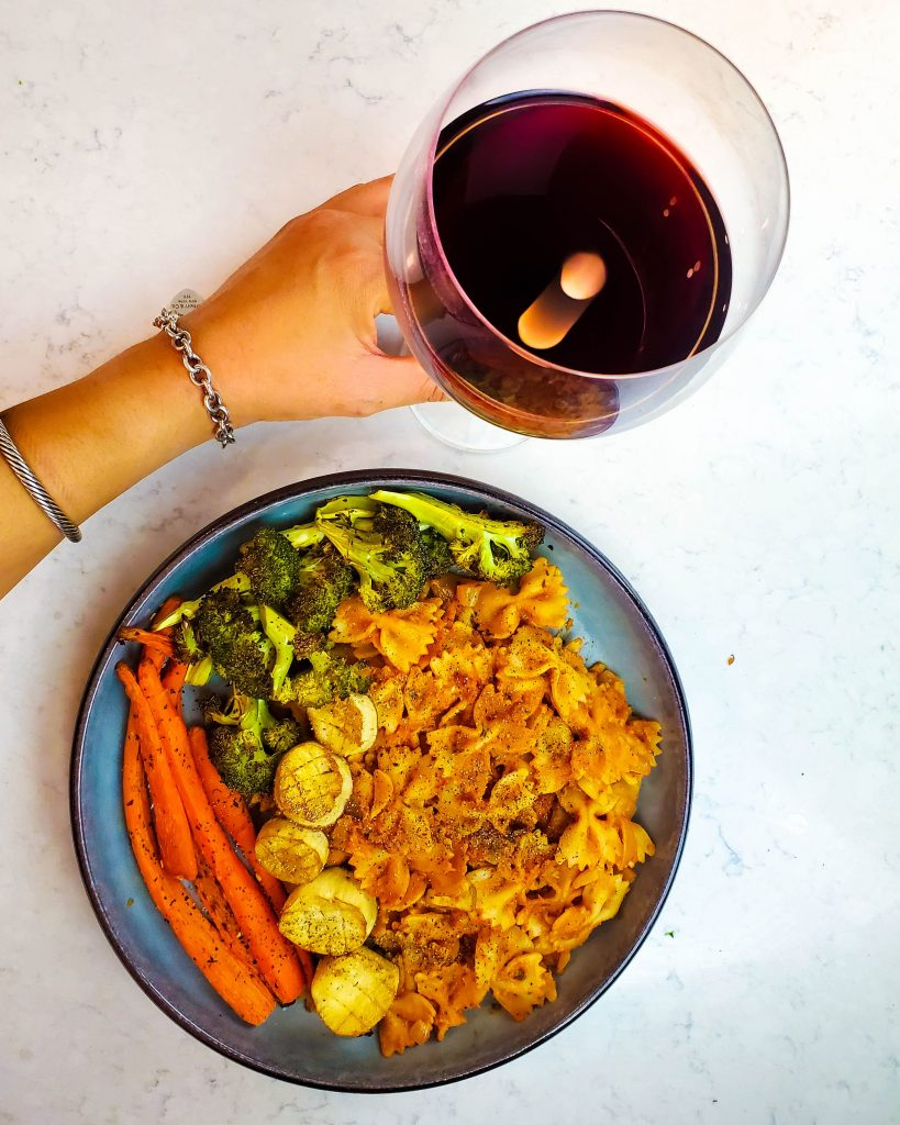 overhead shot of a plate of vegan rosé pasta with roasted vegetables with a hand holding a glass of wine