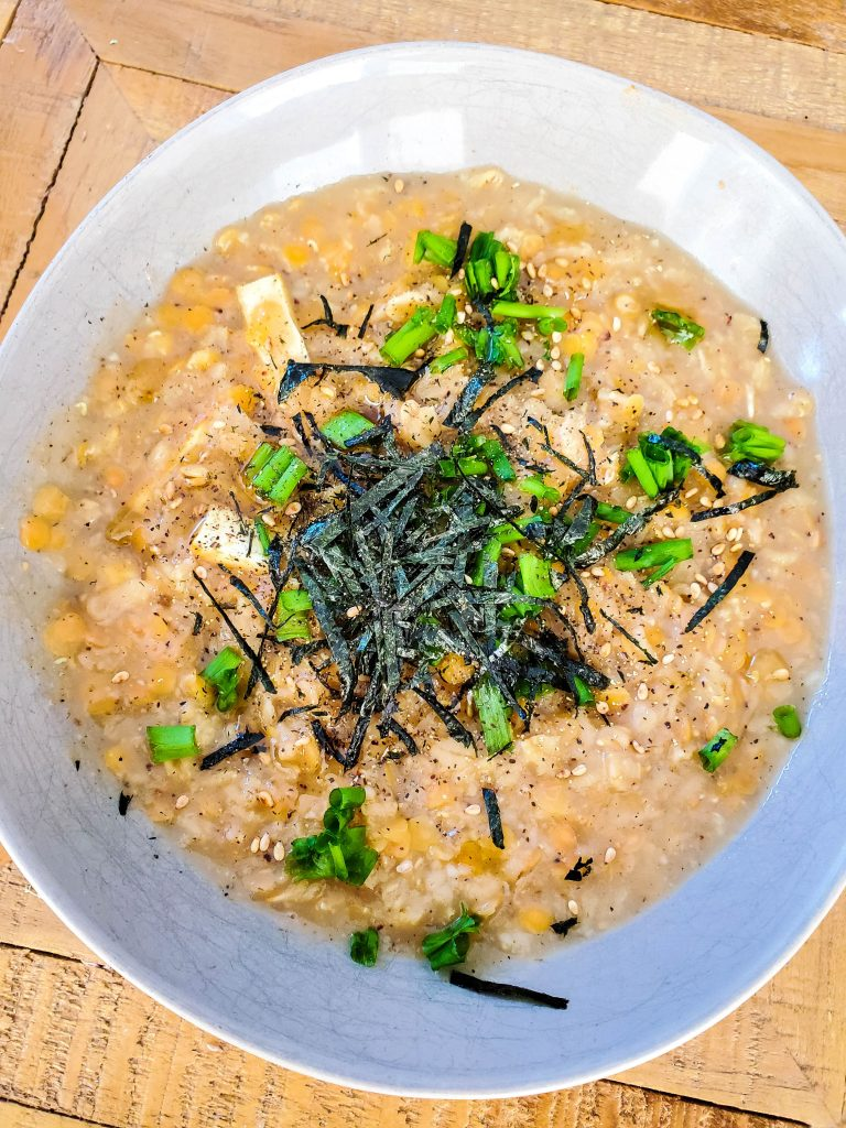 another savoury oatmeal recipe that shows a congee dish topped with nori sheets and green onions