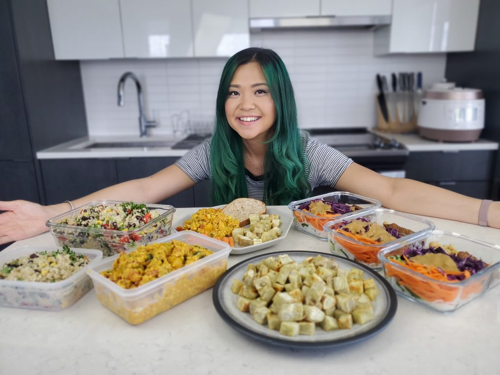 Rose smiling behind the plates of the high protein vegan meal prep recipes she made